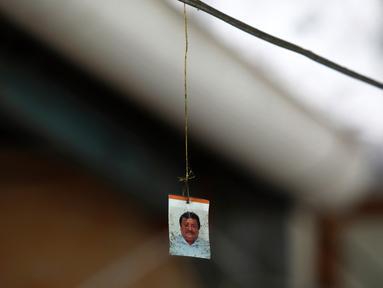 Potret wartawan Leobardo Vazquez yang tergantung di kabel tempat ia ditemukan tewas di depan rumahnya di Gutierrez Zamora, Meksiko (22/3). Vazquez ditemukan tewas terbunuh di dekat kios taco miliknya. (AP/Felix Marquez)