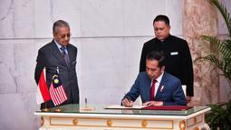 Presiden Joko Widodo menandatangani dokumen disaksikan Perdana Menteri Malaysia Mahathir Mohamad di Putrajaya (8/8/2019). Pertemuan juga membahas masalah WNI di Malaysia hingga kelapa sawit dan kedua pemimpin tersebut akan salat Jumat bersama. (Farhan Abdullah/Department Of Information/AFP)