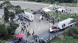 Truk-truk bantuan kemanusiaan untuk Venezuela menuju Jembatan Tienditas di perbatasan Kolombia-Venezuela, Cucuta, Kolombia, Kamis (7/2). Kedatangan bantuan ini disambut gembira oleh sekelompok migran Venezuela. (Edinson ESTUPINAN/AFP)