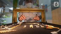 Petugas pegadaian memperlihatkan lelang emas perhiasan di kantor pusat Pegadaian, Jakarta, Selasa (20/4/2021). PT Pegadaian (Persero) terus berupaya memberikan pelayanan kepada masyarakat Indonesia. (merdeka.com/Imam Buhori)