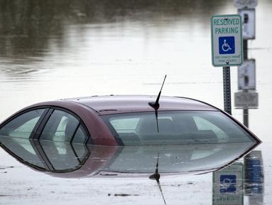 Sebuah mobil terendam air sungai Stillaguamish pasca badai yang melanda negara bagian Washington, (19/11/2015). Hingga saat ini 185.000 rumah tidak disuplai listrik karena masih banyak daerah yang tergenang air. (REUTERS/David Ryder)