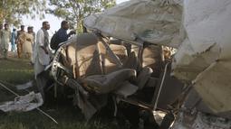 Warga melihat puing-puing bus yang tertabrak kereta api di Farooq Abad, Distrik Sheikhupura, Pakistan, Jumat (3/7/2020). Saksi mata mengatakan bahwa bus berhenti di rel hingga kemudian kereta menabraknya. (AP Photo/K.M. Chaudary)
