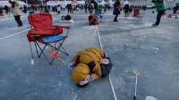 Peserta mengintip keadaan di bawah sungai saat acara Festival Es di sungai Hwacheon yang membeku di Korea Selatan, Sabtu (14/1). (AP Photo/Ahn Young-joon)