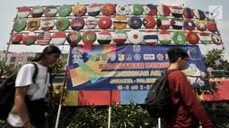 Warga melintas di depan instalasi berupa bendera negara-negara peserta Asian Games 2018, Jakarta, (15/7). Sambut Asian Games, Kelurahan Bungur mempercantik kawasan di pinggir Kali Sunter dengan mengecat warna-warni tembok. (Merdeka.com/Iqbal S. Nugroho)
