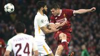 Pemain Liverpool, James Milner menyundul bola dibayangi pemain AS Roma pada laga leg pertama semifinal Liga Champions 2017-2018 di Anfield, Selasa (24/4). Liverpool mengalahkan AS Roma di kandang sendiri dengan skor 5-2.  (Filippo MONTEFORTE/AFP)