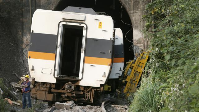 Seorang pekerja berdiri di depan kereta yang tergelincir dekat Ngarai Taroko, Hualien, Taiwan, Sabtu (3/4/2021). Kecelakaan terjadi di rel utara Hualien saat ada truk yang jatuh ke rel kereta yang baru keluar dari terowongan. (AP Photo/Chiang Ying-ying)