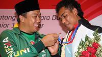 Menpora menyambut kedatangan Zohri di Indonesia dengan kalungan bunga, mengenakan jaket Asian Games 2018 dan menyerahkan secara simbolis uang bonus pembinaan.