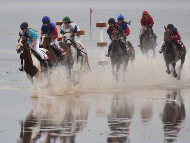 Sejumlah peserta memacu kudanya di atas lumpur saat berkompetisi di Wadden Race, Lower Saxony, Jerman, Minggu (12/7/2015).Para peserta bersaing untuk menjadi yang terdepan. (REUTERS/Fabian Bimmer)