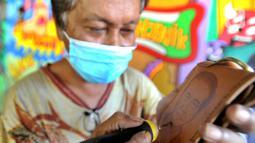 Arfan (55) menyelesaikan karya seni lukis bakar di galeri Rumah Oenik, Kampung Ragamukti, Tajur Halang, Bogor, Senin (28/9/2020). Menggunakan limbah kayu dan kulit yang tidak terpakai Arfan mengubah dengan menggunakan solder listrik  menjadi karya seni yang bernilai tinggi. (merdeka.com/Arie Basuki)