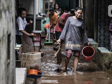 Warga membersihkan lumpur dan sampah saat banjir di permukiman Kebon Pala, Jatinegara, Jakarta, Minggu (25/10/2020). Hampir 12 jam banjir kiriman dari Bogor itu masih merendam permukiman warga di RT 11 RW 05 Kebon Pala dengan ketinggian mencapai pinggang orang dewasa.  (merdeka.com/Iqbal Nugroho)
