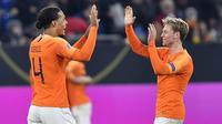 Bek Belanda, Virgil Van Dijk, merayakan gol bersama Frenkie De Jong pada laga UEFA Nations League di Veltins Arena, Gelsenkirchen, Senin (19/11/2018). Kedua tim bermain imbang 2-2. (AP/Martin Meissner)