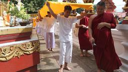 11 anak laki-laki bersama pelatih mereka, yang diselamatkan dari gua di Thailand, menjalani upacara pentahbisan di Kuil Wat Phra That Doi Wao, Selasa (24/7). Sebanyak 11 dari 12 remaja itu menjalani ritual menjadi biksu selama 9 hari. (AP /Sakchai Lalit)