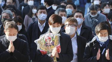 Orang-orang yang mengenakan masker melakukan tradisi doa untuk Tahun Baru pada hari kerja pertama tahun ini di Kuil Kanda Myojin, di Tokyo, Jepang, Senin (4/1/2021).  Orang-orang berdoa untuk mencari keberuntungan dan bisnis yang Makmur. (AP Photo/Koji Sasahara)