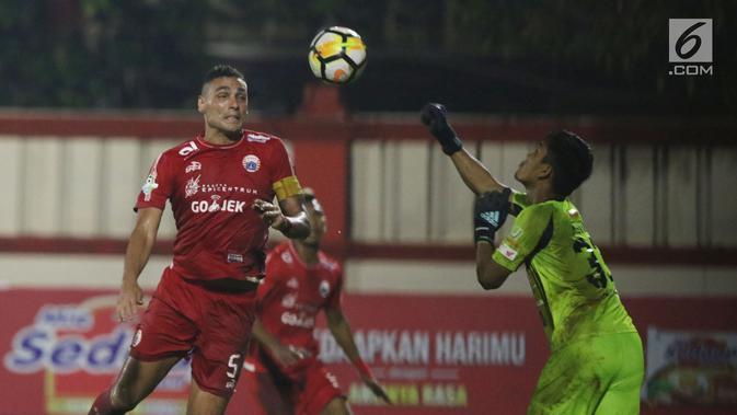Bek Persija, Jaimerson Da Silva Xavier (kiri) berebut bola atas dengan kiper Persebaya, Miswar Saputra pada lanjutan Go-Jek Liga 1 Indonesia 2018 bersama Bukalapak di Lapangan PTIK Jakarta, Selasa (26/6). (Liputan6.com/Helmi Fithriansyah)