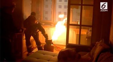 Seorang petugas mencegah terjadinya kebakaran di sebuah apartemen di Liaoning, Tiongkok. Ia membawa tabung gas yang terbakar  dari lantai 9 tanpa menggunakan alat apapun.