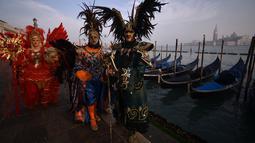 Sejumlah peserta mengenakan topeng dan kostum unik berdiri di St Mark Square selama Karnaval Venesia di Italia, Sabtu (27/1). Karnaval Venesia digelar 40 sebelum Paskah. (FILIPPO MONTEFORTE / AFP)