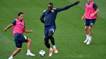 Pelari tercepat dunia, Usain Bolt berebut bola saat berlatih di Central Coast Stadium, Gosford, Australia, (21/8). Bolt akan memulai debutnya di sepak bola Australia dengan bermain untuk Central Coast Mariners. (AFP Photo/Saeed Khan)