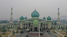 Gambar udara menunjukkan sebuah masjid ketika kabut asap pekat menyelimuti Pekanbaru, Riau, Minggu (15/9/2019). Menurut Data AirVisual, hingga pagi tadi kualitas udara Riau menunjukkan indeks tidak sehat dengan parameter Air Quality Index (AQI) atau indeks kualitas udara 161. (ADEK BERRY/AFP)