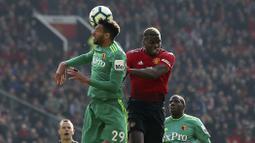 Gelandang Manchester United, Paul Pogba, duel udara dengan pemain Watford, Etienne Capoue, pada laga Premier League di Stadion Old Trafford, Sabtu (30/3). Manchester United menang 2-1 atas Watford. (AP/Martin Rickett)