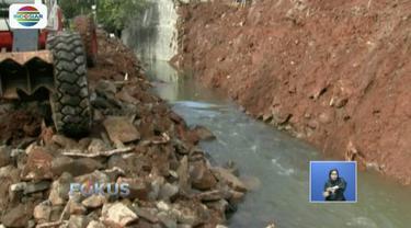 Petugas singkirkan material longsor dari turap yang ambrol di Perumahan Tirta Mandala, Cilodong, Depok.