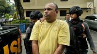 Pelaku pengeroyokan dan penganiayaan, Edwin Hitipeuw dikawal oleh polisi saat dibawa ke Polda Metro Jaya, Jakarta (12/7). Dari hasil pemeriksaan sementara, penganiayaan dilakukan karena motif bersenggolan mobil di jalan Tol Jagorawi. (Liputan6.com/Pool)