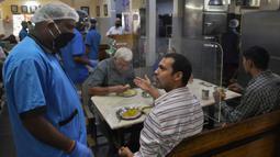 Pelanggan berbincang dengan pramusaji di sebuah restoran yang dibuka kembali usai pelonggaran lockdown di Bangalore, India, Senin (8/6/2020). Untuk keamanan pelanggan, restoran-restoran menyiapkan panel transparan di meja makan sebagai bagian dari rangkaian pencegahan COVID-19. (Manjunath Kiran/AFP)