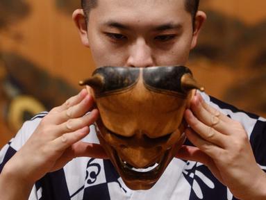"""Kennosuke Nakamori mengenakan topeng """"hannya"""" saat berlatih di Kamakura Noh Theatre, Kamakura, Prefektur Kanagawa, Jepang, 29 Juli 2020. Pandemi COVID-19 telah memengaruhi teater di seluruh dunia, termasuk drama yang diturunkan dari generasi ke generasi sejak abad ke-14 ini. (Philip FONG/AFP)"""