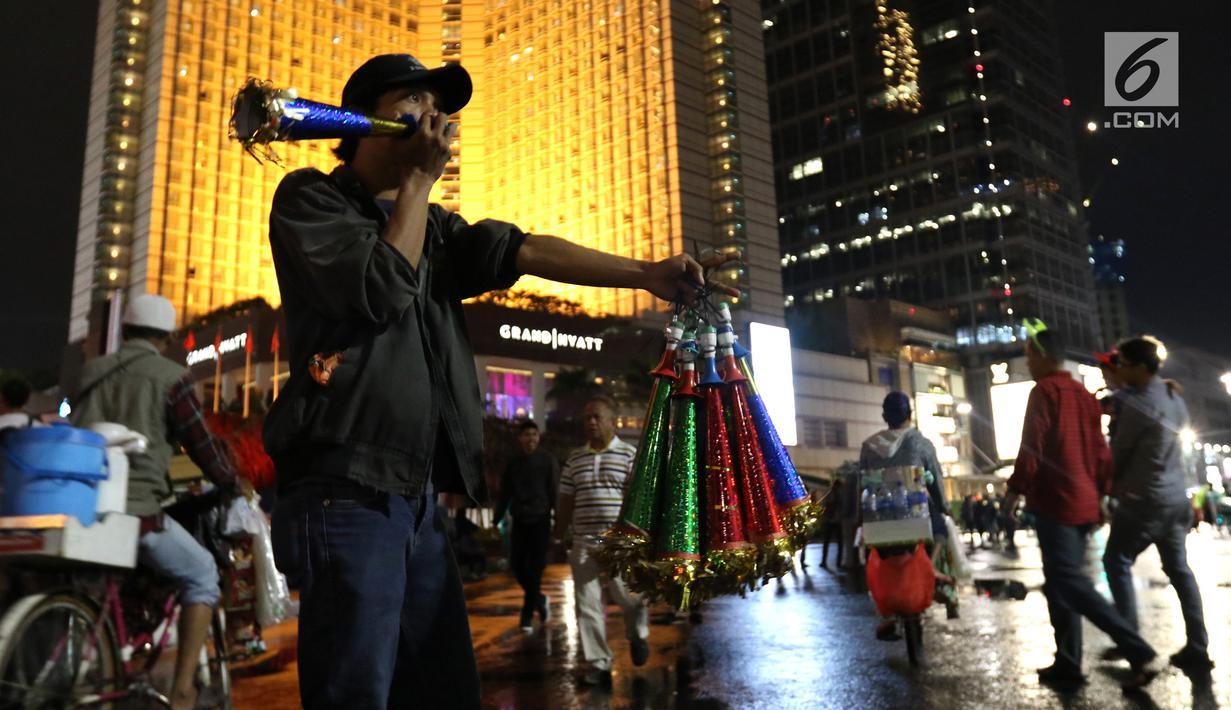 Pedagang menjual terompet pada malam pergantian tahun di kawasan Bundaran HI, Jakarta, Senin (31/12). Pergantian tahun dimanfaatkan pedagang untuk mencari keuntungan dengan berjualan pernak pernik tahun baru.(Liputan6.com/Angga Yuniar)