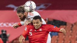 Bek Spanyol, Sergio Ramos, duel udara dengan pemain Swiss, Manuel Akanji, pada laga UEFA Nations League di Stadion St. Jakob-Park, Minggu (15/11/2020). Kedua tim bermain imbang 1-1. (Georgios Kefalas/Keystone via AP)