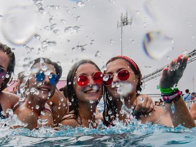 Sejumlah wanita bersuka ria mencipratkan air di kolam renang selama Festival Arenal Sound di Burriana, Spanyol (31/7/2019). Festival musik ini berlangsung dari 30 Juli sampai 4 Agustus 2019.  (AFP Photo/Jose Jordan)