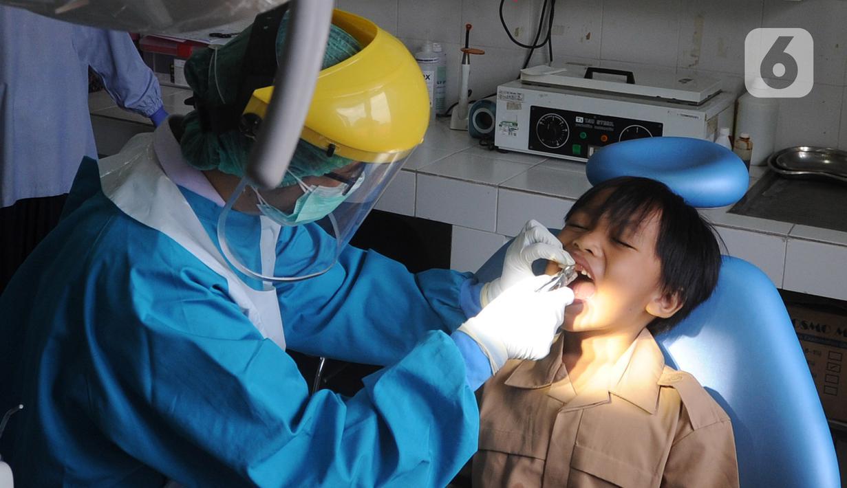 Dokter mencabut gigi murid baru sekolah dasar negeri di Puskesmas Pondok Labu, Jakarta Selatan, Rabu (12/8/2020). Selain dalam rangka Bulan Imunisasi Anak Sekolah, kegiatan ini juga bagian dari pemeriksaan kesehatan menyeluruh kepada murid baru sekolah dasar negeri. (merdeka.com/Arie Basuki)