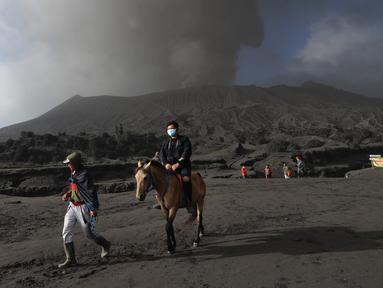 Wisatawan menunggang kuda saat gunung Bromo yang sedang mengalami erupsi di Probolinggo, Jawa Timur, Selasa (26/3/2019). Kawasan wisata Gunung Bromo masih aman dikunjungi wisatawan asalkan tidak melakukan aktivitas di area dalam radius satu kilometer dari kawah Gunung Bromo (merdeka.com/Arie Basuki)