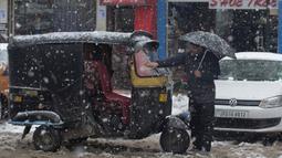 Seorang pria Kashmir membersihkan salju dari bajajnya di Srinagar, Kashmir yang dikuasai India (15/1/2020). Menurut pejabat sipil Baseer Khan, Jalur listrik rusak dan banyak jalan terkubur di bawah salju yang mempengaruhi aktivitas warga sehari-hari. (AP Photo/Dar Yasin)