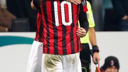 Striker AC Milan, Gonzalo Higuain memeluk gelandang Hakan Calhanoglu usai mencetak gol ke gawang SPAL pada lanjutan Liga Serie A Italia di stadion San Siro (29/12). Gol Higuain memberi kemenangan tipis Milan atas SPAL 2-1. (AP Photo/Antonio Calanni)