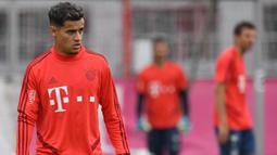 Pemain Bayern Munchen, Philippe Coutinho, mengamati instruksi saat latihan perdananya di Munchen, Selasa (20/8). Bintang Brasil ini didatangkan dari Barcelona. (AFP/Christof Stache)
