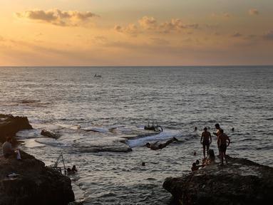Sejumlah orang berenang di laut Mediterania dari Corniche, atau promenade tepi laut saat matahari terbenam selama hari terakhir musim panas, di Beirut, Lebanon (20/9). (AP Photo / Hussein Malla)
