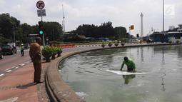 Petugas membersihkan busa yang mencemari kolam air mancur di bundaran patung kuda, Jakarta, Rabu (28/3). Kegiatan tersebut rutin dilakukan setiap busa-busa muncul di genangan air mancur. (Liputan6.com/Arya Manggala)