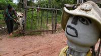 Seorang perempuan mendirikan orang-orangan sawah di depan rumahnya di provinsi Kampong Cham, Kamboja, 11 Oktober 2020. Penduduk di desa itu mebuat orang-orangan sawah atau disebut juga Tim Mong untuk menangkal virus corona  Covid-19 berdasarkan kepercayaan yang mereka yakini. (TANG CHHIN Sothy/AFP)