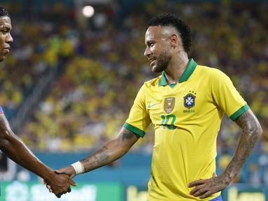 Striker Brasil, Neymar Jr, bersalaman dengan striker Kolombia, Orlando Berrio, usai laga persahabatan di Stadion Hard Rock, Florida, Jumat (6/9). Kedua negara bermain imbang 2-2. (AFP/Rhona Wise)