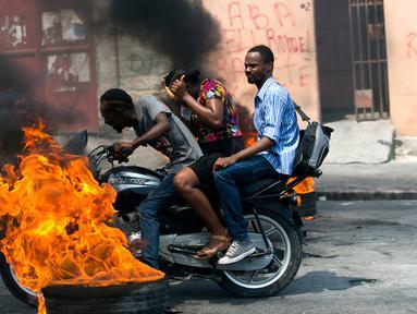 Pengendara sepeda motor melewati barikade ban yang terbakar saat terjadi protes krisis bahan bakar di Port-au-Prince, Haiti, Senin (16/9/2019). Krisis bahan bakar menyebabkan transportasi umum tidak beroperasi. (AP Photo/Dieu Nalio Chery)