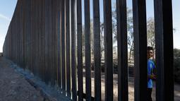 Seorang anak laki-laki melihat-lihat pagar perbatasan Amerika Serikat (AS) dengan Meksiko di Calexico, California, AS, Minggu (5/3). Kontrak kerja pembuatan pembatas di lokasi itu didapat di era kepemimpinan Presiden Donald Trump.(AP Photo/Gregory Bull)