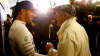 Lewis Hamilton dan Sir Jackie Stewart, sama-sama pengoleksi tiga gelar juara dunia F1 asal Inggris yang bertemu usai F1 GP AS di Sirkuit The Americas, Austin, AS, Senin (26/10/2015) dini hari WIB. (Reuters/Mike Stone)