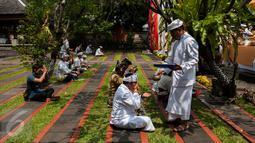 Umat Hindu meminum air suci (tirta) dalam prosesi Tawur Agung Kesanga di Pura Aditya Jaya, Jakarta, Senin (27/3). Prosesi Tawur Agung tersebut merupakan rangkaian perayaan Hari Raya Nyepi tahun baru saka 1939. (Liputan6.com/Gempur M Surya)