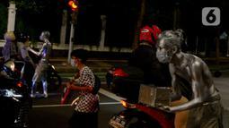Manusia silver saat menghibur pengendara bermotor di perempatan kawasan Senayan, Jakarta, Sabtu (9/5/2020). Meskipun di tengah pandemi Covid-19, para manusia silver ini masih tetap melakukan aksinya di jalanan untuk memenuhi kebutuhan sehari-hari. (merdeka.com/Imam Buhori)