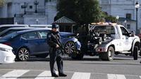 Pihak berwenang menderek mobil setelah seorang pria menabrakkannya ke barikade di Capitol Hill, Washington, Amerika Serikat, Jumat (2/4/2021). Garda Nasional dan polisi langsung menjaga ketat Kantor Kongres AS itu. (AP Photo/Jose Luis Magana)