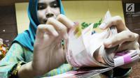 Petugas teller menghitung uang di Bank Bukopin Syariah, Jakarta, Selasa (30/1). Di periode sama, pertumbuhan aset perbankan konvensional sebesar 11,20% menjadi Rp 7.183,77 triliun. (Liputan6.com/Angga Yuniar)