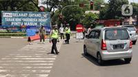 Polisi mengatur lalu lintas saat pengendalian mobilitas ganjil genap untuk pengunjung TMII di Jalan Pintu 1 TMII, Jakarta, Sabtu (18/9/2021). Pembatasan mobilitas pada TMII dan Taman Impian Jaya Ancol dilakukan pada hari Jumat-Minggu mulai pukul 12.00-18.00 WIB. (Liputan6.com/Herman Zakharia)