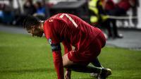 Bomber Portugal, Cristiano Ronaldo terkapar pada laga kedua kualifikasi Piala Eropa 2020 yang berlangsung di Stadion Da Luz, Lisbon, Senin (27/3). Portugal raih hasil imbang 1-1 kontra Serbia. (AFP/Patricia de Melo)