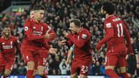 Penyerang Liverpool, Roberto Firmino berselebrasi bersama rekannyya usai mencetak gol ketiganya lewat titik penalti ke gawang Arsenal pada lanjutan Liga Inggris di Anfield Stadium (29/12). Liverpool menang telak atas Arsenal 5-1. (AP Photo/Rui Vieira)