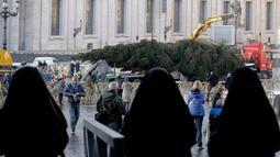 Biarawati mengamati pohon Natal raksasa yang hendak didirikan di Lapangan Santo Petrus, Vatikan, Kamis (22/11). Tahun ini, pohon Natal itu baru akan diresmikan pada 7 Desember dan lampunya tetap menyala hingga 13 Januari 2019. (AP/Andrew Medichini)